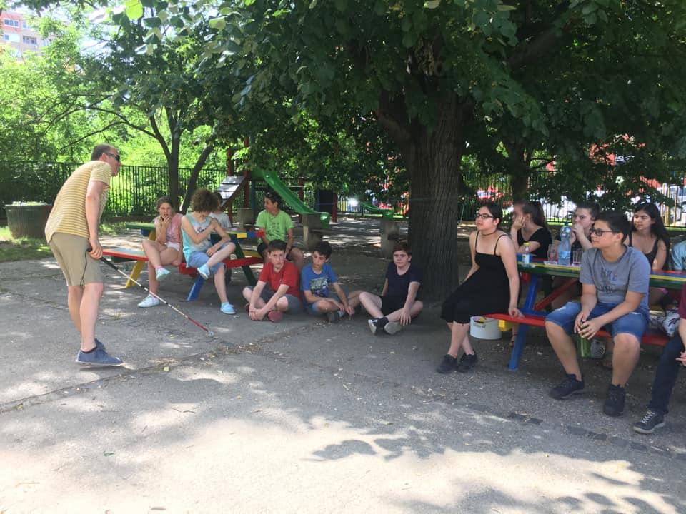 A kép egy a táborban elkapott pillanatkép. Gyerekek ülnek körben, Szabolcs láthatóan nagy beleéléssel mutogat. Jó hangulatú, önfeledt pillanat.
