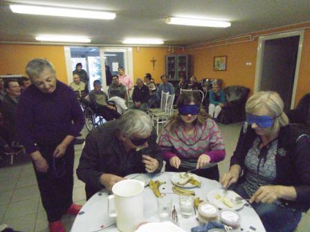 Életkép az érzékenyítésről. Az otthon közösségi termében egy asztalt körbeülve próbálják ki a szemfedőt viselő lakók, a késsel-villával történő banánevést.