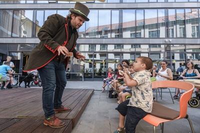 Az Art Hotel épülete előtt gyereket ülnek sorban egymást mellett, közben egy bűvész szórakoztatja őket. A gyerkőcök láthatóan nagyon élvezik az előadását, mosolyogva tapsolnak.